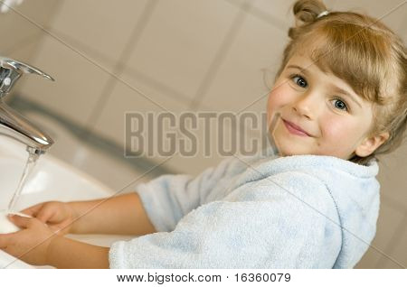 Little girl washing hands in bathroom