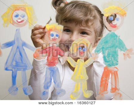 Little girl painting family on glass