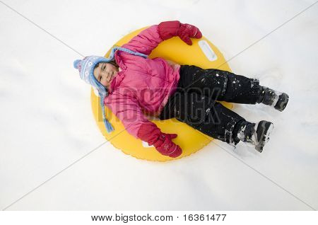 Little girl sliding downhill on tube