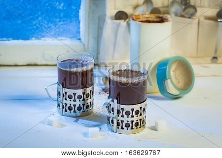 Hot Cup And Coffee Pot With Spoons By Frozen Window