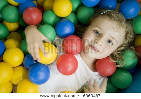 Linda garota jogando em bolas coloridas