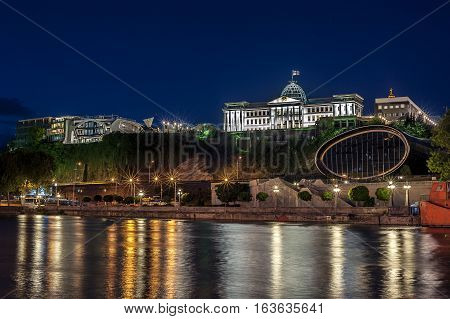 Georgia Tbilisi night . View from the right bank of the Kura River in the complex of the Presidential Palace and the new concert hall .