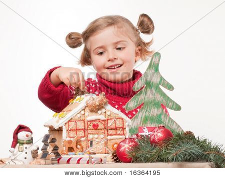 Cute girl decorating oneself made christmas cookies house