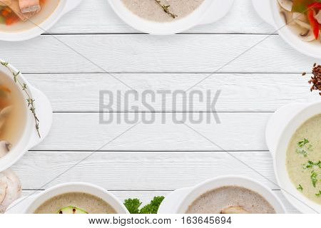 Different tasty soups frame on white wood flat lay. Top view on empty wooden table with variation of restaurant hot dishes. Worldwide cuisine, healthy food, buffet, lunch, menu concept