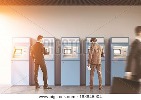 Hallway of an office or a bank. A man is rushing by. Two businessmen are standing near ATM machines. There is a cityscape on the foreground. Toned image.