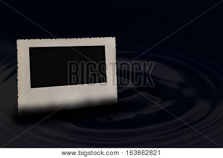 Bevelled old vintage photo frame with jagged edges horizontally partially submerged in the water which forms a circle wave in dark hues. Free place for your text is in the right side of the photo.