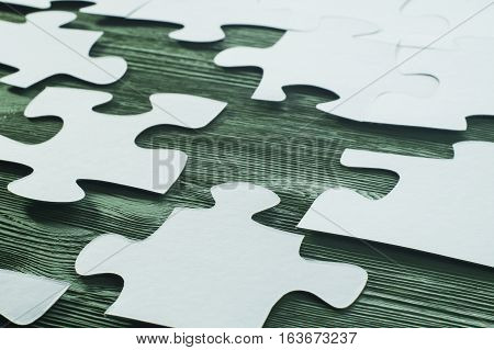 White jigsaw puzzle on a wooden background.  The concept of logical thinking. Logical conundrum. Placing missing a piece of puzzle.