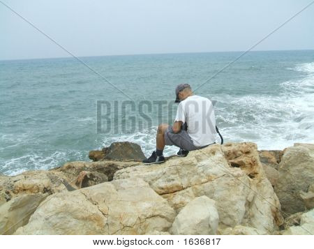 Man Sitting Alone On The Beach