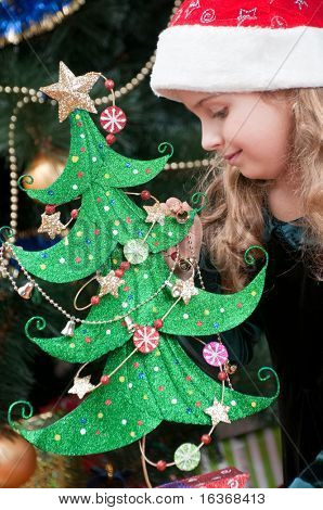 Happy little girl in Santa hat decorating Christmas tree