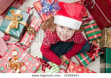 Little girl in Santa hat with Christmas presents