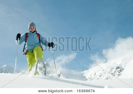 Snowshoeing - woman trekking in winter mountains - space for text