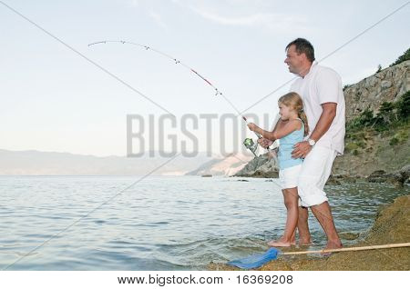 Little girl fishing with father at the beach