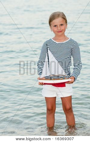 Little girl playing with yacht model in the sea