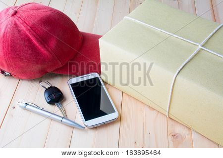 The red cap, parcel post, white paper, pen, smart phone and key of car on bark table