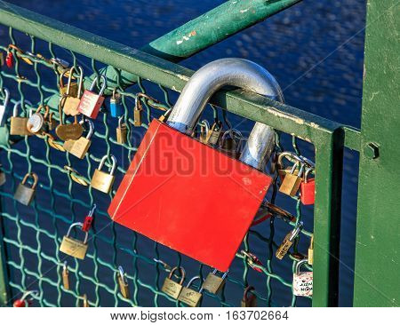Zurich, Switzerland - 1 January, 2017: padlocks on the fence of the Muhlesteg bridge over the Limmat river, selective focus on the large red one. The fence of the bridge is a popular place for couples to hang padlocks, symbolizing their feelings.