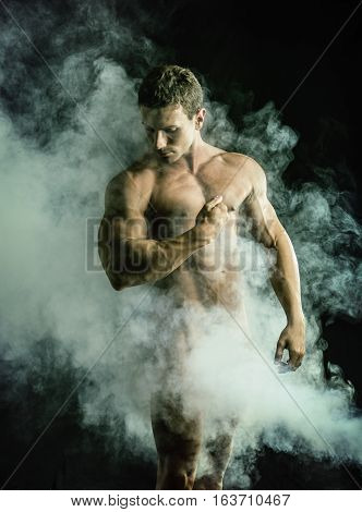 Totally naked male bodybuilder with smoke hiding genitalia, looking away to a side, on dark background