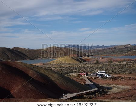 A walkway winds through the colored hills with a pond and parking area at the Painted Hills Unit in the John Day Fossil Beds in Eastern Oregon on a sunny Spring day.