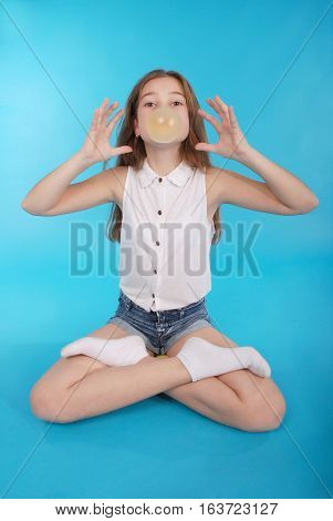 Young girl making a big bubble with a chewing gum isolated on blue