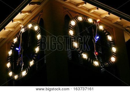 Clock tower with two clocks on two sides lit up in the darkness of the night