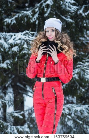 Beautiful young woman in a red jumpsuit in the winter on the background of fir trees.