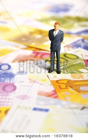 businessman miniature figurine standing on euro banknotes