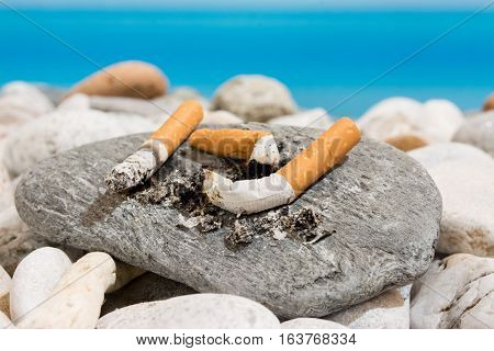Cigarette butts on the beach, pollution concept