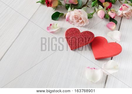 Valentine background with pink rose flowers petals and handmade wooden hearts on white rustic wood. Happy lovers day mockup, copy space
