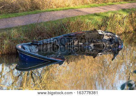 Bow of partially submerged canal boat after fire. Damaged hull of narrow boat in Kennet and Avon Canal after being gutted by fire