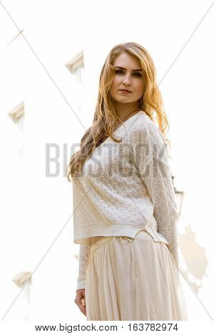 Caucasian white female model portrait and house in the background. Beautiful girl long red hair beige skirt and cardigan. Woman old town building