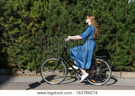 Beautiful young woman and vintage bicycle summer. Red hair girl riding the old black retro bike outside in the park. Having fun in the city