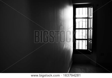 Light coming through a window and reflecting into the wall of a room, black and white.