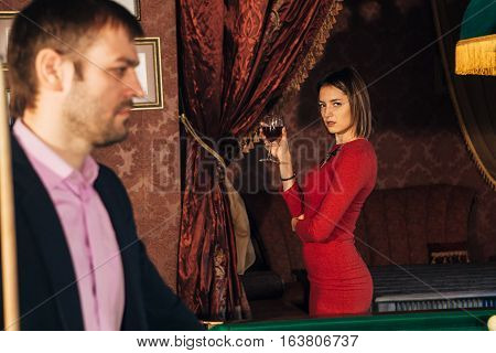 beautiful woman in a red dress watching the game of Billiards, handsome serious man playing pool, a man prepares the cue to play Billiards