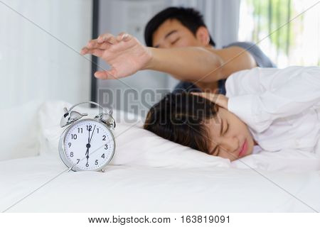 Sleepy man trying turn off alarm clock beside a woman annoyed by noisy alarm clock in the morning