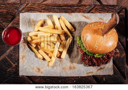 Ideal feeding. Top view of burger and French fries standing on table while being served with pita and sauce in restaurant.
