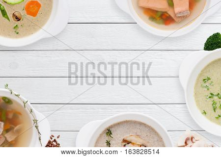 Frame of different soups on white wooden table. Buffet serving of restaurant hot dishes, free space for text. Worldwide cuisine, healthy food, lunch, menu concept