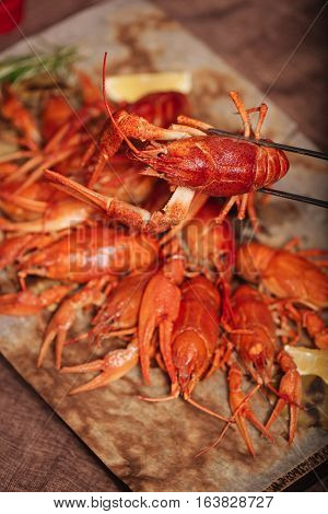 Come and eat. Crayfishes being served in restaurant with rosemary and lemon while lying on a pita.