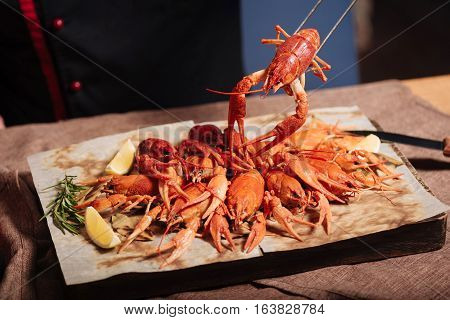 Visit us. Crayfishes being served in restaurant while lying on a pita with rosemary and lemon.