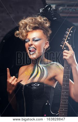 Impressed woman punk showing metal horns. Rocker girl in courage posing at camera with her bass guitar, bright makeup and hairstyle. Subculture, lifestyle, art, music, drive concept