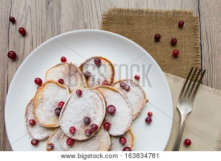 Home made pancakes with cranberries and sugar powder on a white plate. Wooden table rustic decoration berries and a fork. Top view flat lay view from above