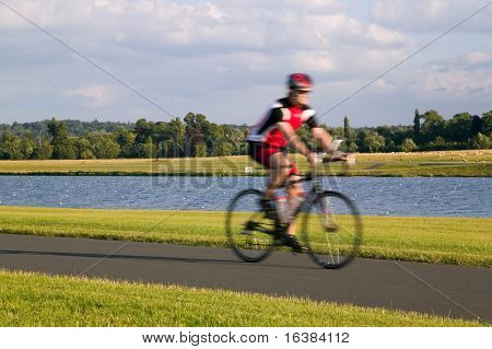 Man on a bicycle going for a ride on a summers evening. Deliberate motion blur.