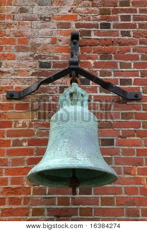 Very old bronze 17th century bell on a bracket situated on the wall of a coastal fortress built by Henry VIII in England. Showing signs of suffering from Verdigris.