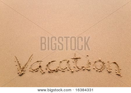 The word 'Vacation' written in sand at the beach.