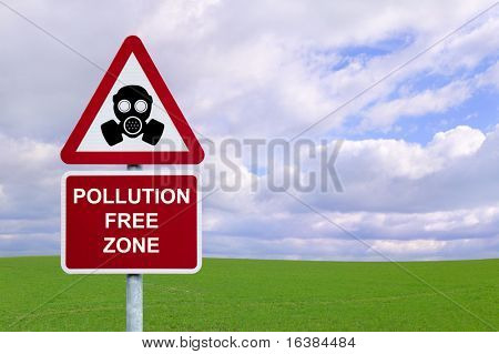 Image of a sign for a 'Pollution Free Zone' against a green field and blue cloudy sky.  Environmental and Conservation concepts.