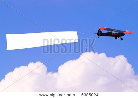 An airplane flying through the sky pulling a blank white banner to add your own message.