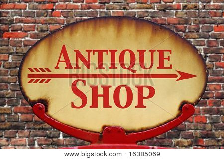 A rusty old retro arrow sign with the text Antique shop