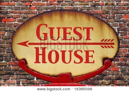 A rusty old retro arrow sign with the text Guest house