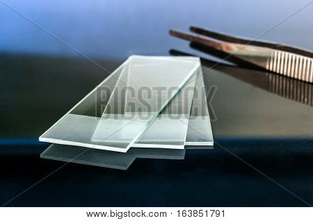 Microscope glass slides reflecting on glass table with pliers on the background