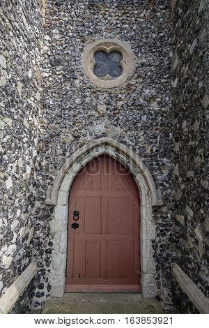 A wooden church door set on an old stone wall