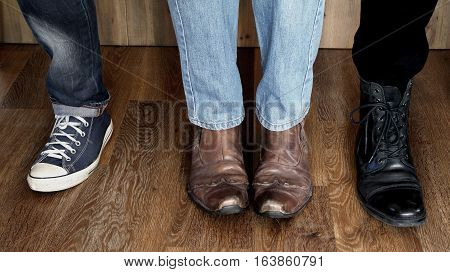 Guys wearing three classic styles of men's boots on wooden background