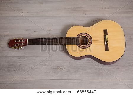 Guitar on wooden background fretboard, string musical instrument close-up